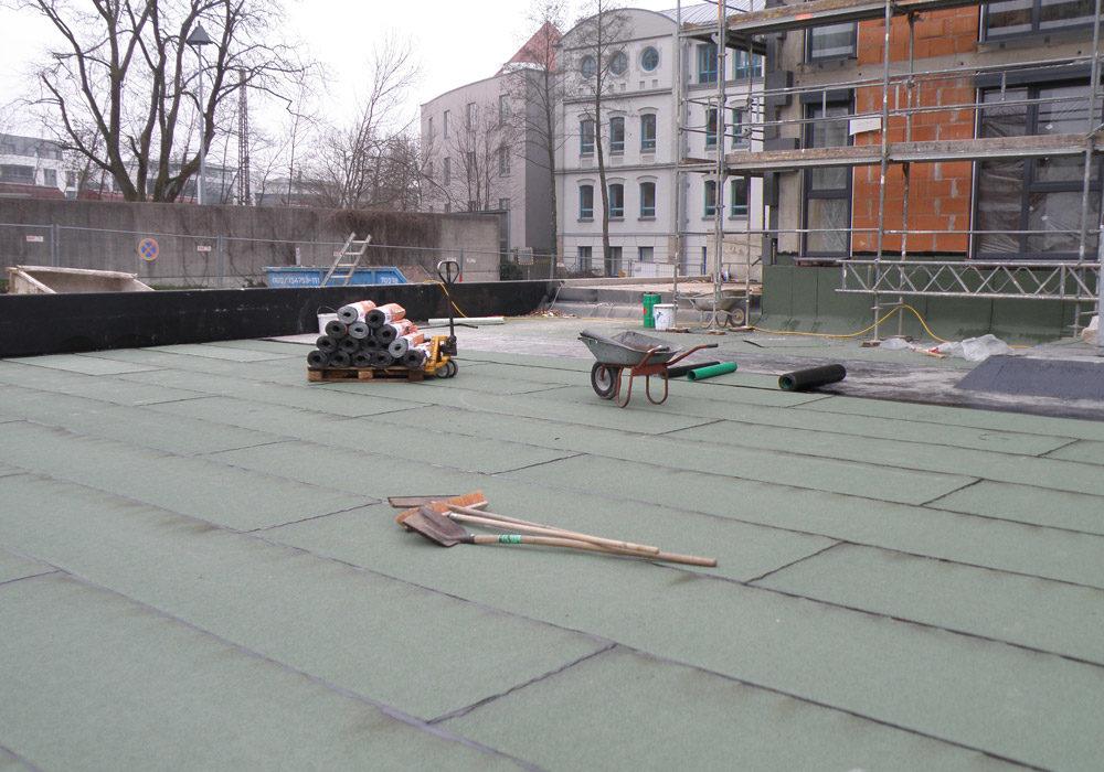 Auf einem Flachdach finden gerade Abdichtungsarbeiten statt.