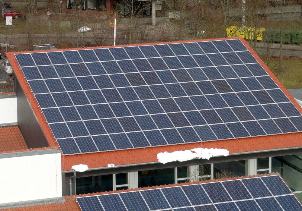Ziegeldach einer Halle, verdeckt durch eine Solaranlage.