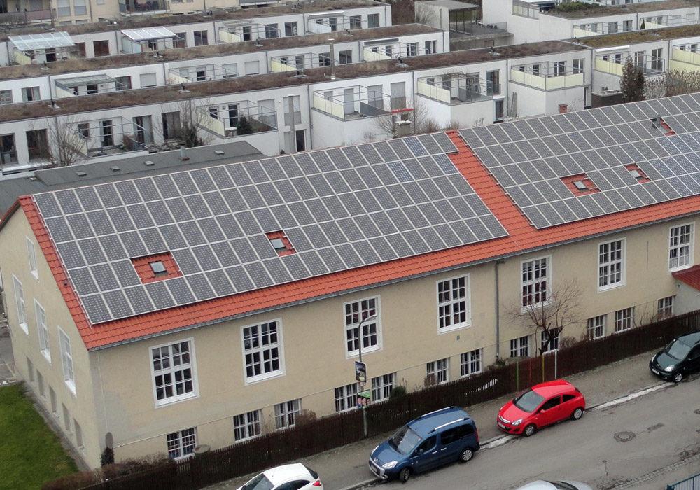 Mehrfamilienhäuser mit neuem Dach und Solaranlagen.